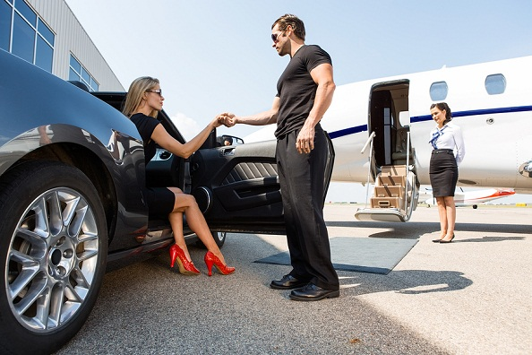 rich woman get out of a car and get ready for go aboard.